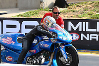 Jul. 19, 2013; Morrison, CO, USA: NHRA Matt Smith helps wife, pro stock motorcycle rider Angie Smith line up her bike during qualifying for the Mile High Nationals at Bandimere Speedway. Mandatory Credit: Mark J. Rebilas-
