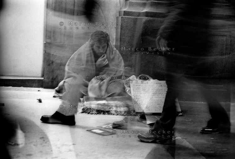 milano, un mendicante in corso vittorio emanuele, via dello shopping in centro città --- milan, a beggar in vittorio emanuele street, shopping street in downtown