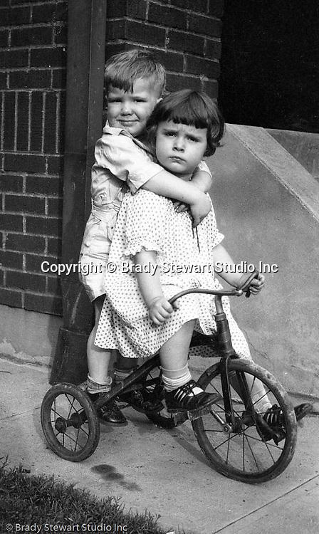 Wilkinsburg PA:  Helen Stewart neighbors riding their tricycle on the sidewalk.