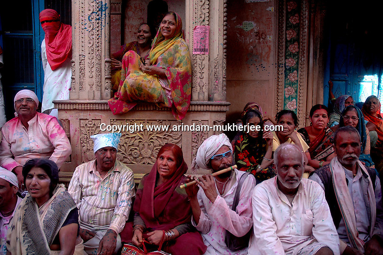 Visitors wait for the lathmar holi to start while a flute player plays his flute, Uttar Pradesh, India on the day of Lathmar holi. Lathmar holy is celibrated 7 days before the actual holi day.