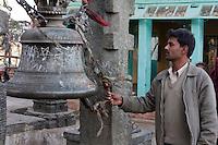 Kathmandu, Nepal.  Nepali Worshipper Rings a Bell at Swayambhunath Temple.  Bells drive evil spirits away.