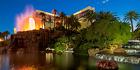 Mirage hotel with its artificial volcano erupting and reflecting on the cascade water, during twilight in Las Vegas Nevada
