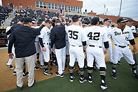 The Wake Forest Demon Deacons huddle up around head coach Wake Forest Demon Deacons head coach Tom Walter (16) prior to the game against the Sacred Heart Pioneers at David F. Couch Ballpark on February 15, 2019 in  Winston-Salem, North Carolina.  The Demon Deacons defeated the Pioneers 14-1. (Brian Westerholt/Four Seam Images)
