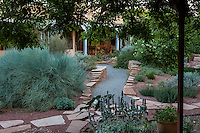 Gravel path between flagstone garden walls leading from dining patio to vine covered shade structure in backyard New Mexico garden, design by Judith Phillips