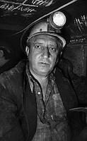 Sangerhausen / DDR - 1989.Miniera di rame Thomas Munzer. 700 metri di profondità. Con i minatori a bordo di un trenino che porta gli operai nella zona di estrazione, sul fronte della miniera. Si viaggiava per quasi un'ora in un cunicolo buio alla sola luce delle lampade ad acetilene. Poi si proseguiva carponi. Le gallerie erano alte un metro. Le ginocchia affondavano nel fango. Le squadre di minatori lavoravano 24 ore suddivisi in turni di 8 ore. A causa delle dure condizioni di lavoro, numerosi operai si ammalavano di silicosi e reumatismi ed andavano in pensione in anticipo. In compenso i loro stipendi erano i più alti della DDR. Dopo la reunificazione della Germania la miniera Thomas Munzer è stata chiusa..Foto Livio Senigalliesi..Sangerhausen / DDR - Dec.1989.Thomas Munzer copper mine. In a tunnel 700 meters depth. Workers on board a small train that brought them to work on the front of the mine. Working conditions were very hard. They worked on their knees in the dark using the lamp of acetylene. Teams of miners worked 8 hours in 3 shifts. After the unification of Germany Thomas Munzer copper mine was closed and has now become a museum..Photo Livio Senigalliesi .