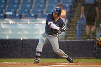 Carlos Cortes (2) of Oviedo High School in Oviedo, Florida playing for the Tampa Bay Rays scout team bats in the rain during the East Coast Pro Showcase on July 27, 2015 at George M. Steinbrenner Field in Tampa, Florida.  (Mike Janes/Four Seam Images)