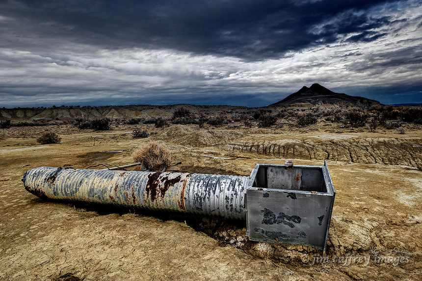 An old eroded catch basin and culvert left abandoned in the Cabezon Wilderness Study Area of northwestern New Mexico with Cerro Cuate in the background.
