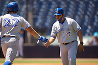 Dunedin Blue Jays manager Luis Hurtado congratulates Addison Barger (22) as he rounds the bases after hitting a home run during a game against the Tampa Tarpons on May 9, 2021 at George M. Steinbrenner Field in Tampa, Florida.  (Mike Janes/Four Seam Images)