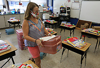 Rhonda Walton, a first grade teacher at Asbell Elementary School, prepares supplies Wednesday, August 19, 2020, for her incoming students in her classroom at the school in Fayetteville. School starts on August 24 in a continuation of the pandemic that closed in-class learning last spring. This year, schools have been told to be ready for both virtual and in-class and be ready to switch up proportions of each if necessary. Check out nwaonline.com/200823Daily/ and nwadg.com/photos for a photo gallery.<br /> (NWA Democrat-Gazette/David Gottschalk)