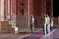 Agra, India.  Taj Mahal Mosque.  Men Praying, Imam in front leading the Prayer.