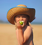 Girl, 4 years old, wearing a straw hat, eating an  apple on  the beach