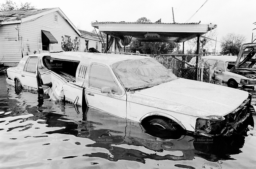 USA. Louisiana. New Orleans. Orleans Parish. 9th Ward area. The 9th Ward used to be the living place of the black (afro-american) community . Aftermath of hurricane Katrina. Two white limousine cars (typical american limousine with extra length of the car) have been destroyed by the floods, like all houses of the area. The area is empty and all its inhabitants have left the town. The people could no longer and ever live again in the houses because of the destructions due to the floods and the water. The entire area needs to be bulldozed before any new construction can be built. Pollution and contaminated land. Household waste. Destruction of the urban american way of life. © 2005 Didier Ruef