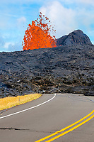 Pohoiki Road is interrupted by a fountain of hot lava spewing from Fissure 15 of the east rift zone of Kilauea Volcano during the eruption which began May 3, 2018 in Leilani Estates subdivision near Pahoa, Puna, Big Island, Hawaii, USA, burnt and broken utility poles with their guy wires and attachments are pushed along at the flow edge, and the road is cracked from deformation caused by lava flowing underground