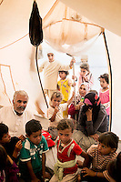 Children and adults crowd together inside a tent. Approximately two million people have fled the conflict in Syria. At least 130,000 of them live in Zaatari Refugee Camp, although it was designed to house 60,000, and a further 2,000 people arrive each day.