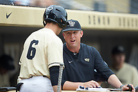 Wake Forest Demon Deacons assistant coach Bill Cilento (37) chats with Michael Turconi (6) during the game against the Miami Hurricanes at David F. Couch Ballpark on May 11, 2019 in  Winston-Salem, North Carolina. The Hurricanes defeated the Demon Deacons 8-4. (Brian Westerholt/Four Seam Images)