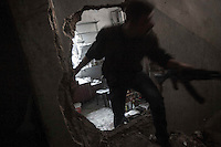 In this Saturday, Nov. 03, 2012 photo, a rebel fighter belonging to the Qatebee Sokor Al-Islam sneaks through buildings as rebels repel a coordinated attack by mortar, tank and aerial artillery carried out by loyalists to President Bashar Al-Assad during heavy clashes in the nearby Castel Harami battlefield in the Jdeide district of Aleppo, the Syrian's largest city. (AP Photo/Narciso Contreras).