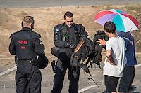 """Nach den pogromartigen Ausschreitungen gegen eine Fluechtlinsunterkunft im saechschen Heidenau am Freitag den 21. August 2015 durch Anwohnerinnen der Ortschaft, kamen am Samstag de 22. August 2015 ca. 250 Menschen in die Ortschaft um ihre Solidaritaet mit den Gefluechteten zu zeigen.<br /> Am Vorabend hatten Rassisten, Nazis und Hooligans sich zum Teil Strassenschlachten mit der Polizei geliefert um zu verhindern, dass Fluechtlinge in einen umgebauten Baumarkt einziehen. Ueber 30 Polizisten wurden dabei verletzt.<br /> Bis in die Abendstunden des 22. August blieb es trotz spuerbarer Anspannung um die Unterkunft ruhig. Im Laufe des Tages wurden immer wieder Gefluechtete mit Reisebussen gebracht was von den wartenenden Heidenauern mit Buh-Rufen begleitet wurde. Vereinzelt wurde auch """"Sieg Heil"""" gerufen, was die Polizei jedoch nicht verfolgte.<br /> Kurz vor 23 Uhr griffen Nazis und Hooligans dann wie am Vorabend die Polizei mit Steinen, Flaschen, Feuerwerkskoerpern und Baustellenmaterial an. Die Polizei mussten mehrfach den Rueckzug antreten, scheuchte den Mob dann von der Fluechtlingsunterkunft weg. Dabei wurden auch wieder Traenengasgranaten verschossen. Mindestens ein Nazi wurde festgenommen.<br /> Im Bild: Die Polizei kontrolliert akribisch die Teilnehmer der antirassistischen Kundgebung.<br /> 22.8.2015, Heidenau<br /> Copyright: Christian-Ditsch.de<br /> [Inhaltsveraendernde Manipulation des Fotos nur nach ausdruecklicher Genehmigung des Fotografen. Vereinbarungen ueber Abtretung von Persoenlichkeitsrechten/Model Release der abgebildeten Person/Personen liegen nicht vor. NO MODEL RELEASE! Nur fuer Redaktionelle Zwecke. Don't publish without copyright Christian-Ditsch.de, Veroeffentlichung nur mit Fotografennennung, sowie gegen Honorar, MwSt. und Beleg. Konto: I N G - D i B a, IBAN DE58500105175400192269, BIC INGDDEFFXXX, Kontakt: post@christian-ditsch.de<br /> Bei der Bearbeitung der Dateiinformationen darf die Urheberkennzeichnung in den EXIF- und IPTC-Daten ni"""