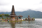 """The Hindu temple of Ulun Danu at Candikuning is one of the iconic images of Bali, Indonesia.  Located in the high hills of the Bedugul, about 30 miles north of Bali's capital city of Denpasar, the temple is built on the shores of the crater Lake Bratan (formed from the sunken crater of a long-dormant volcano).  Much of the inner precincts of the temple is closed to the (non-Hindu) public, but the gardens are spectacular and feature fabulous shrines, statuary, and views.  The iconic tourist image is the two """"water shrines,"""" which these days are usually partially submerged in the waters of Lake Bratan."""