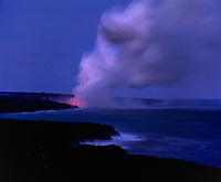 Lava Flowing into Pacific Ocean and steam plume at night, Volcanoes National Park, Big Island, Hawaii, USA.