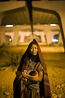 A portrait of 28 year old Lali holding her 12 day old baby Mia, beneath the IIT flyover where they sleep.