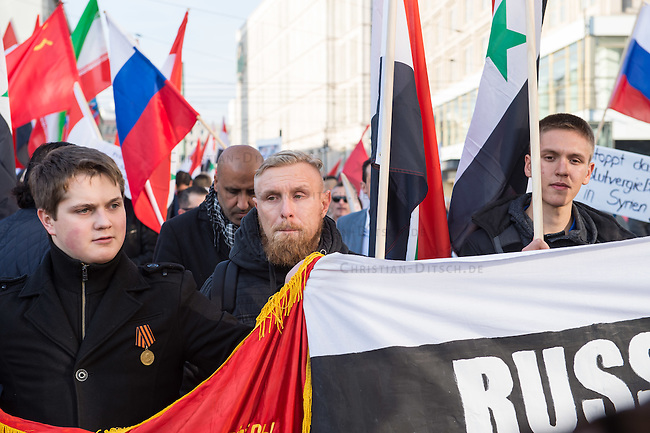 """250 bis 300 Menschen demonstrierten am Samstag den 31. Oktober 2015 in Berlin fuer die Unterstuetzung des syrischen Diktators Assad durch Russland. Sie trugen Fahnen Syriens, der ehemaligen Sowietunion, Russlands, Nordkoreas, der DDR, des Iran und Venezuelas, die sich """"alle zusammen gegen den Imperialismus zur Wehr setzen"""" wuerden. Russlands Praesident Putin wurde ausdruecklich fuer sein Militaerengagement gedankt, das Eingreifen der USA verurteilt.<br /> In der Bildmitte mit Bart: Marc Kluge, laut Szeneinsidern ist er langjaehriger Neonaziaktivist. In Magdeburg, war er fuer den """"Selbstschutz Sachsen-Anhalt"""" aktiv und NPD-Kandidat.<br /> 31.10.2015, Berlin<br /> Copyright: Christian-Ditsch.de<br /> [Inhaltsveraendernde Manipulation des Fotos nur nach ausdruecklicher Genehmigung des Fotografen. Vereinbarungen ueber Abtretung von Persoenlichkeitsrechten/Model Release der abgebildeten Person/Personen liegen nicht vor. NO MODEL RELEASE! Nur fuer Redaktionelle Zwecke. Don't publish without copyright Christian-Ditsch.de, Veroeffentlichung nur mit Fotografennennung, sowie gegen Honorar, MwSt. und Beleg. Konto: I N G - D i B a, IBAN DE58500105175400192269, BIC INGDDEFFXXX, Kontakt: post@christian-ditsch.de<br /> Bei der Bearbeitung der Dateiinformationen darf die Urheberkennzeichnung in den EXIF- und  IPTC-Daten nicht entfernt werden, diese sind in digitalen Medien nach §95c UrhG rechtlich geschuetzt. Der Urhebervermerk wird gemaess §13 UrhG verlangt.]"""