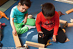 Education Preschool3-4 year olds girl and boy playing with animals and blocks, girl talking to herself