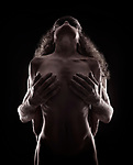 Fine art nude portrait of a couple making love, Tantra and sacred sensuality spiritual concept, silhouette of naked bodies on black background Image © MaximImages, License at https://www.maximimages.com