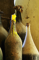 Chateau de Lascaux, Vacquieres village. Pic St Loup. Languedoc. Old dusty bottles in the window. France. Europe. Bottle. One with a burnt down candle.