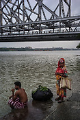 A man sits to brush his teeth while a woman waits on the ghats of river Hooghly in Howrah, Kolkata, West Bengal  on Friday, May 26, 2017. Photographer: Sanjit Das
