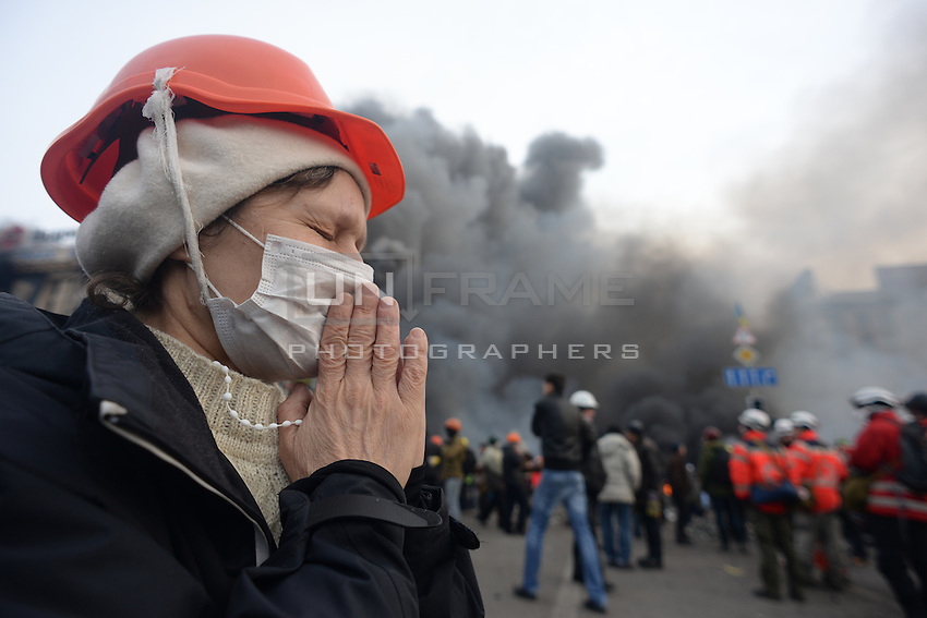 An elder woman prays holding a rosary during the most violent moments of the clashes in Maidan square.  Kiev, Ukraine