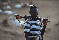ETHIOPIA, Southern Nations, Lower Omo valley, Kangaten, village Kakuta, Nyangatom tribe, shepherds give water to their goats from water holes at dry river Kibish, the shepherds carry Kalashnikov AK-47 machine guns to protect themselves from cattle raids of Turkana tribe / AETHIOPIEN, Omo Tal, Kangaten, Dorf Kakuta, Nyangatom Hirtenvolk, Hirten traenken das Vieh aus Wasserloechern am trocknen Fluss Kibish, die Hirten tragen Kalaschnikow AK-47 Maschinengewehre zum Schutz vor Viehdiebstaehlen durch Turkana Voelker