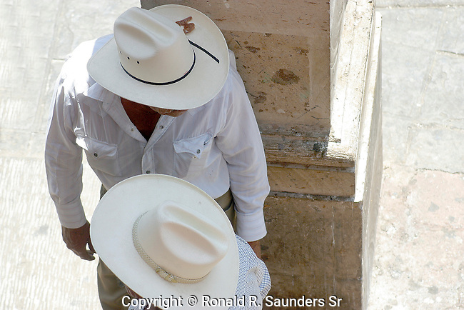 TWO MEXICAN MEN CONVERSE IN MARKETPLACE