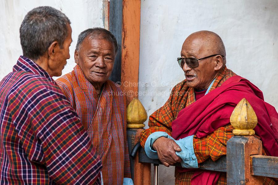 Bumthang, Bhutan.  Old Men Talking, Wearing Traditional Gho.  Jambay Lhakhang Monastery.