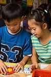 Education Elementary School Grade 1 boy and girl using math manipulatives, pattern blocks