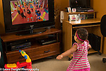 18 month old toddler girl at home watching dance show on television imitating dancers and dancing
