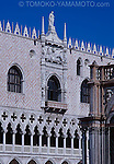 The west facade of Doges' Palace, a Venetian Gothic structure,  showing a sculptrual relief of a doge and St. Mark's lion above a balcony.  A row of pinnacles on the roof against a blue sky is striking  and a row of quatrefoil patterns on tracery on the gallery windows is contrasting. Pink mosaic fa?de is clear. Photo of Architecture in Venice, Italy by Tomoko Yamamoto<br /> Original on 35mm slide film.