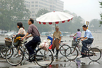 Traffic warden watching cyclists passing by in the rain, Beijing, China.