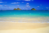 Mokulua Islands with blue sky, blue-green waters, sandy beach and gentle waves from Lanikai beach.