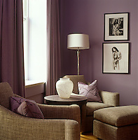In the living room of an apartment in New York lilac walls and curtains are combined with the gold upholstery of two armchairs creating a simple yet stunning effect