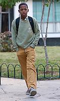 Cuba, Havana.   Cuba's Young Generation.  Teenage Boy Going to School.  Ochre-yellow pants or skirt indicate secondary school level.