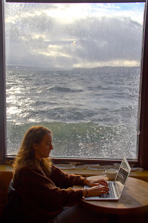 Port Townsend, Better Living Through Coffee, waterfront coffeehouse, women with laptop, winter waves, high tide, Washington State, Pacific Northwest, United States,