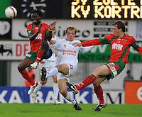 SV Zulte-Waregem - KV Kortrijk..Rob Claeys (midden) haalt de bal weg voor Ernest Nfor (links) en Tarmo Neemelo (rechts)..foto David Catry /VDB