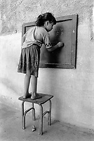 State of Palestine. West Bank. Balata Camp. Palestinian refugees. A young girl, standing on a stool, is drawing sketches with a white chalk on a blackboard during a a military curfew imposed by the Israel Defense Forces (IDF, also called Tzahal or the military forces of the State of Israel). The curfew can last for days and can only be lifted by the IDF when they decide to do it.  Balata Camp is a Palestinian refugee camp established in the northern West Bank in 1950, adjacent to the city of Nablus. It is the largest refugee camp in the West Bank. Balata Camp is densely populated with 30,000 residents in an area of 0.25 square kilometers. In 1991, Balata Camp was living under Isreal's occupation and rules as part as the Occuppied Territories. In the 1980s and 1990s, Balata residents played a leading role in the uprisings known as the First Intifada and the Second Intifada. Balata Camp is since 1993 under palestinian authority, located in the A zone. The Palestinian National Authority (PA or PNA) was the interim self-government body established to govern Areas A and B of the West Bank as a consequence of the 1993 Oslo Accords. Following elections in 2006, its authority had extended only in areas A and B of the West Bank. Since January 2013, the Fatah-controlled Palestinian Authority uses the name State of Palestine on official documents. © 1991 Didier Ruef