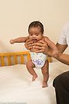 6 week old newborn baby boy held upright by father, reflex: stepping