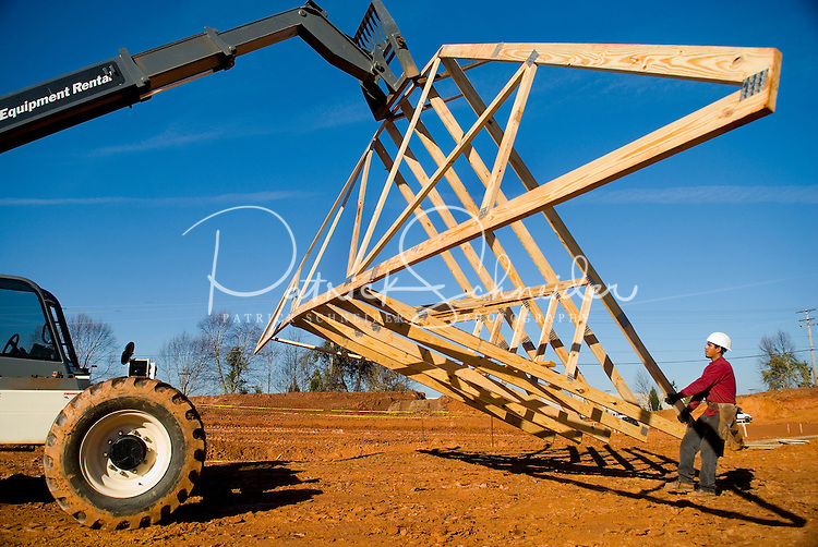 02/22/07:  A construction worker readies a wooden rafter structure to be attached during expansion/construction of a Charlotte-area shopping center. Charlotte, NC, is one of the country's fastest-growing cities. ..By Patrick Schneider- Patrick Schneider Photography.
