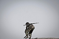 A KIA soldier climbs up to the highest top of an historical Japanese outpost used in the 2nd World War as he keeps watching the enemy's position in Maiya Jang front line at the top of the mountains, the second largest city under control of the Kachin Independence Army. The KIA positions around the city have been attacked by shelling and heavy artillery during months. Fierce clashes have taken place since the ceasefire was broken out by the Burmese army last June 2011. During months the fighting were spread out along the Kachin State leaving more than 40,000 displaced persons and refugees (a conservative estimating) in accord with the humanitarian aid groups.