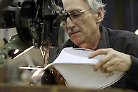 20 January 2005: Glenn Hanson, an employee for 32 years, sews and stitches balls at the Wilson football factory where Super Bowl footballs are made Thursday January 20, 2005 in Ada, Ohio.<br />
