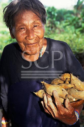 Koatinemo Village, Brazil. Smiling elderly Assurini Indian woman holding sweet potatoes. Para State.