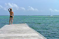 Woman in swimsuit contemplating ocean from pontoon, Punta Cana, Dominican Republic