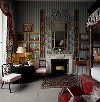 The walls of this bedroom are covered in striped wall paper and a collection of Worcester plates dating from 1800 hangs around the gilt-framed mirror above the fireplace